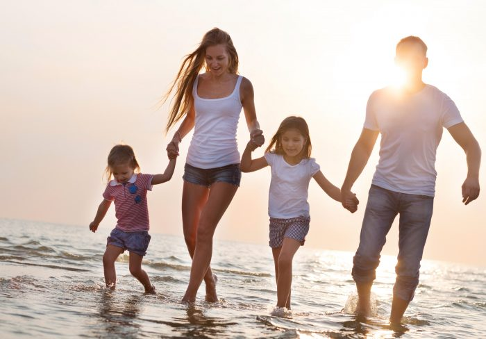 Happy young family having fun running on beach at sunset